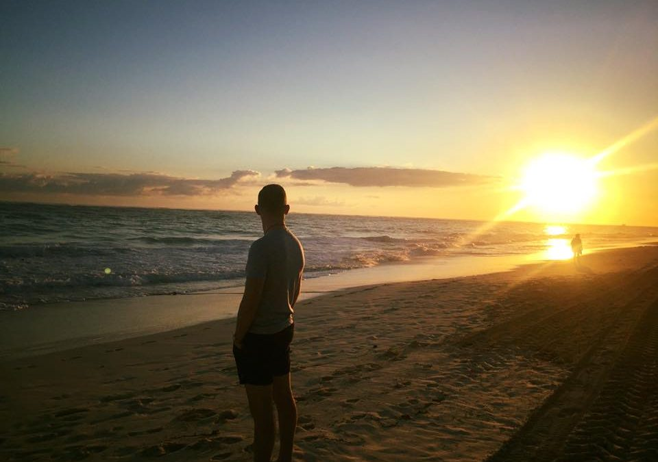 An image of Dan Holloway on a sandy beach watching the sun set with his hands in his pockets